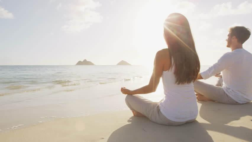 pessoas meditando na praia