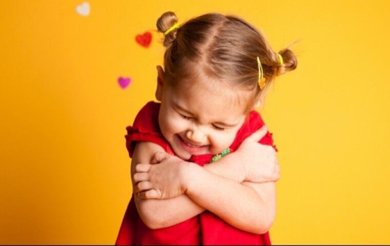 criança se auto abraçando