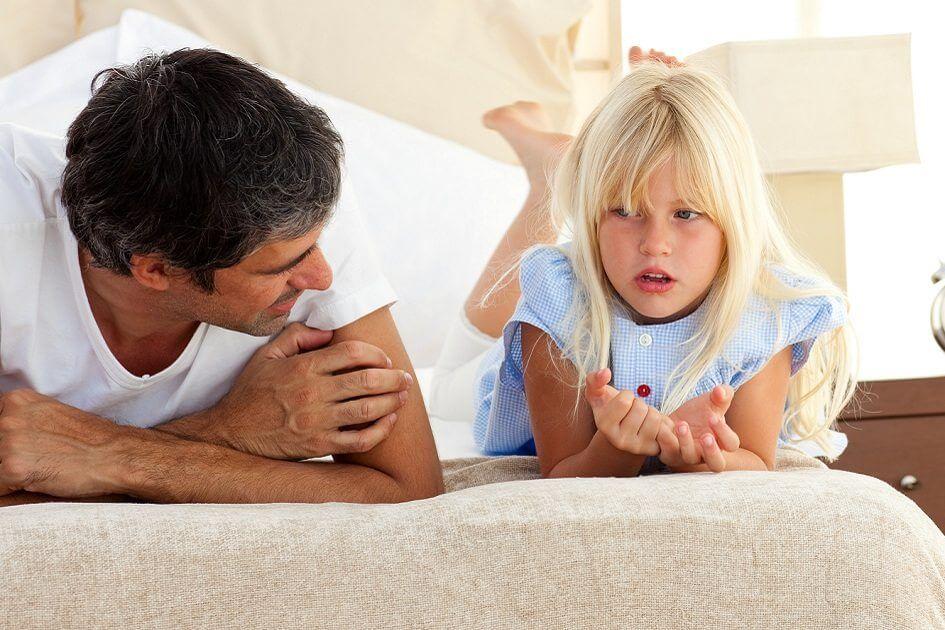 pai conversando com a filha na cama