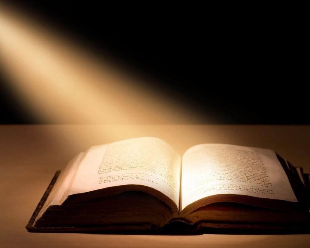bíblia em cima de uma mesa com uma luz sobre ela