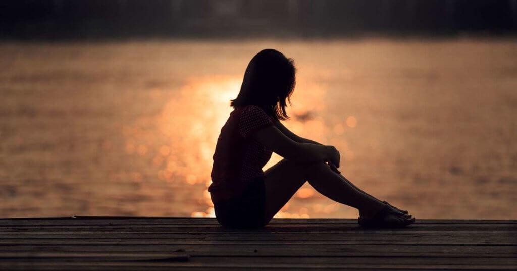 Foto em silhueta em pôr do Sol. Mulher sentada de perfim em um deque de madeira.
