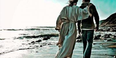 dois homens andando na areia da praia