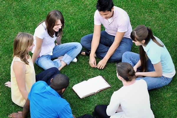 pessoas sentadas na grama falando sobe a bíblia
