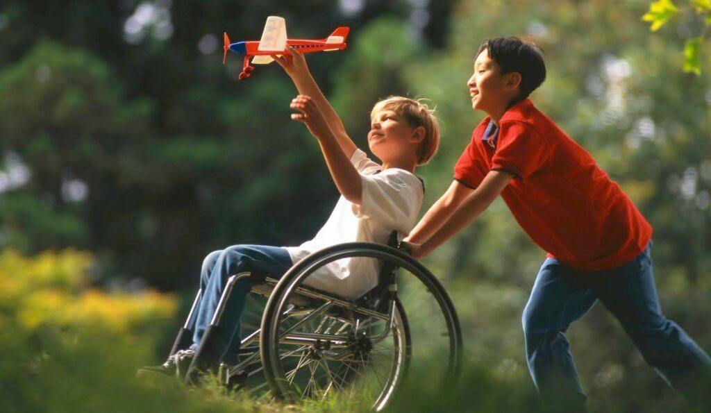 menino ajudando outro na cadeira de rodas