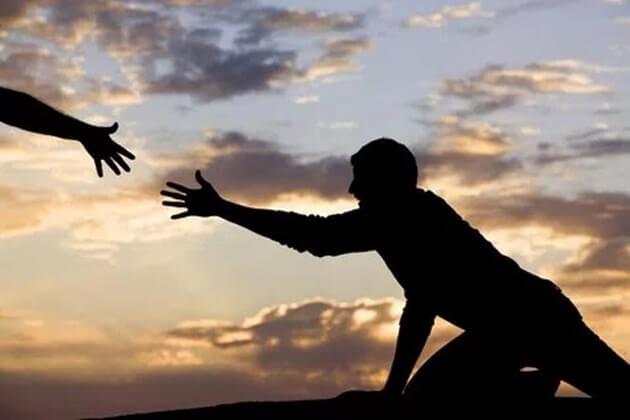 Imagem em silhueta. Homem caído estendendo a mão e uma mão do outro lado estendida para ajudar.