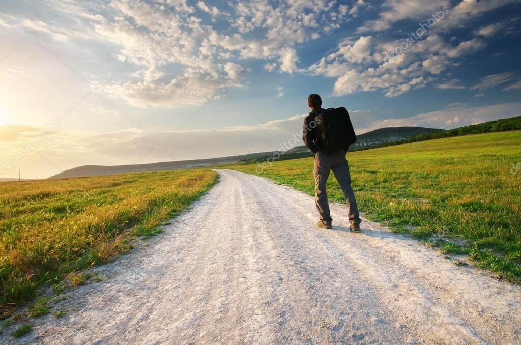 homem com uma mochila numa estrada de terra