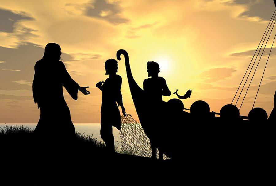 Imagem em silhueta de Jesus e dois pescadores em um entardecer na praia.