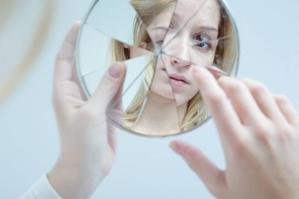 mulher olhando pro espelho quebrado