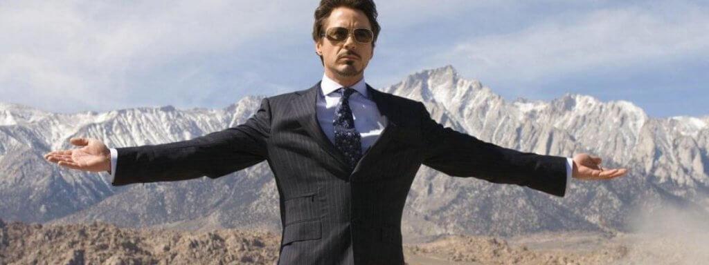 homem de braço aberto no topo da montanha