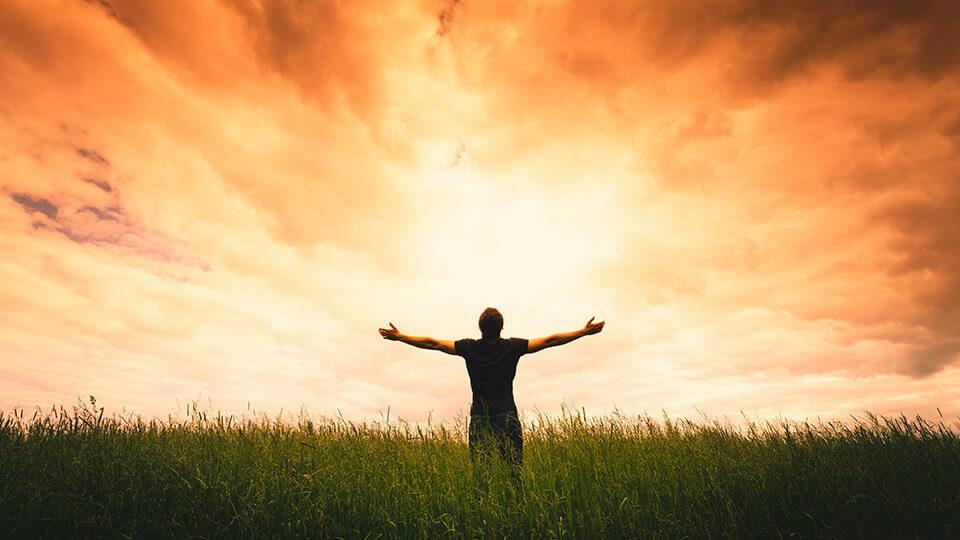 homem com os braços erguidos em um campo