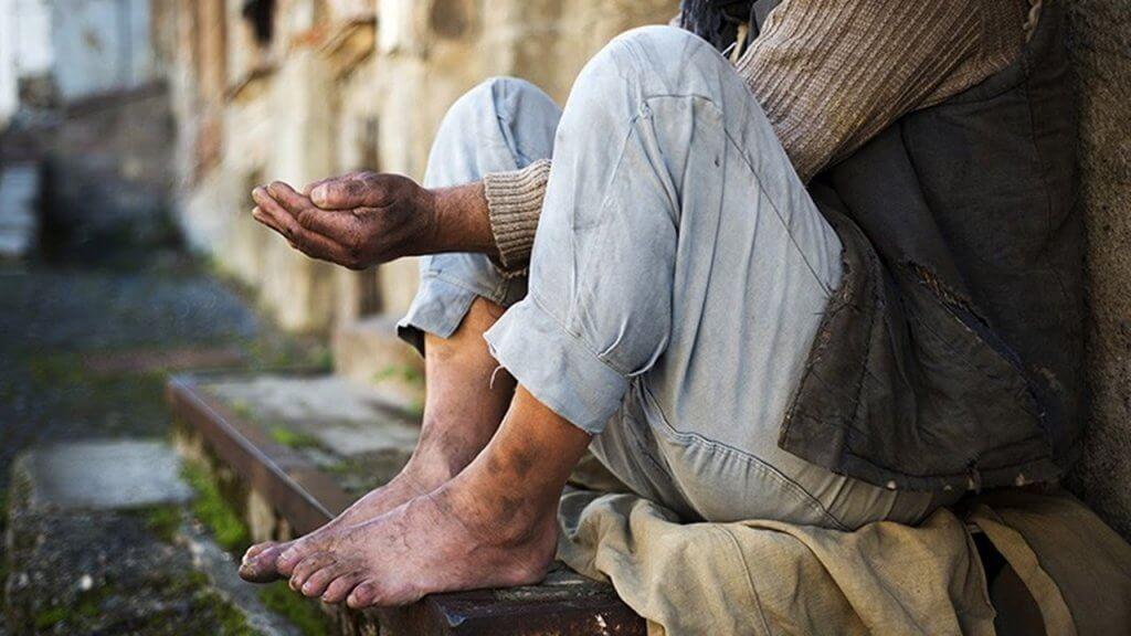 Pessoa sentada na calçada com roupas velhas e sujas. As mãos sujas estendidas em direção à rua como quem pede ajuda.