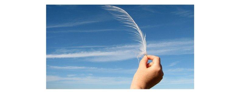 Fundo azul do céu com nuvens brancas. Uma mão segurando uma pena branca.