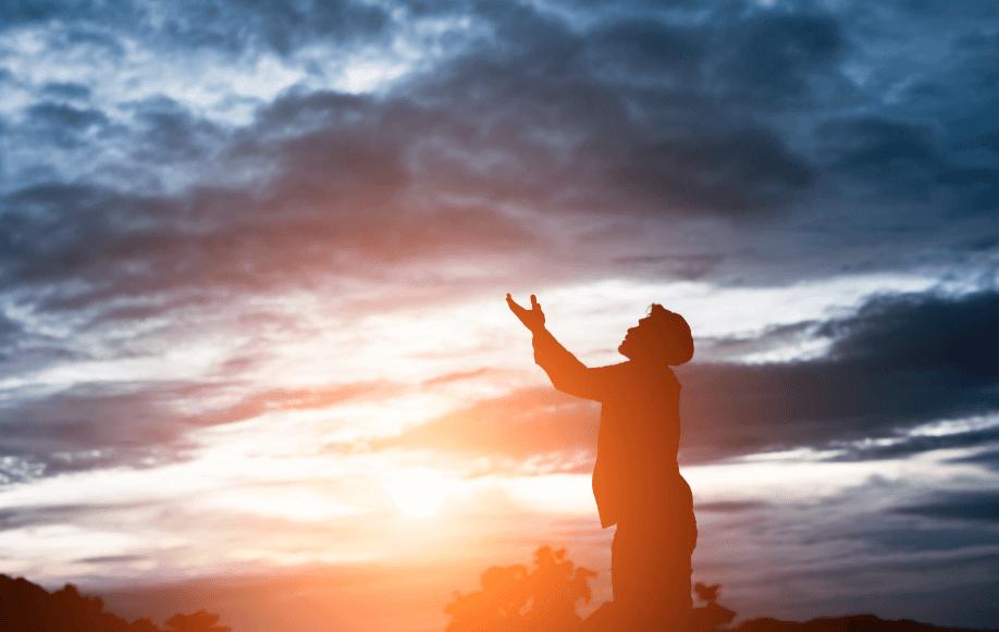 homem ajoelhado em um pico olhando pro céu