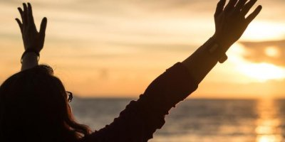 pessoa com os braços erguidos em frente ao mar