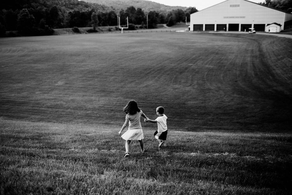 duas crianças de mãos dadas em um campo gramado