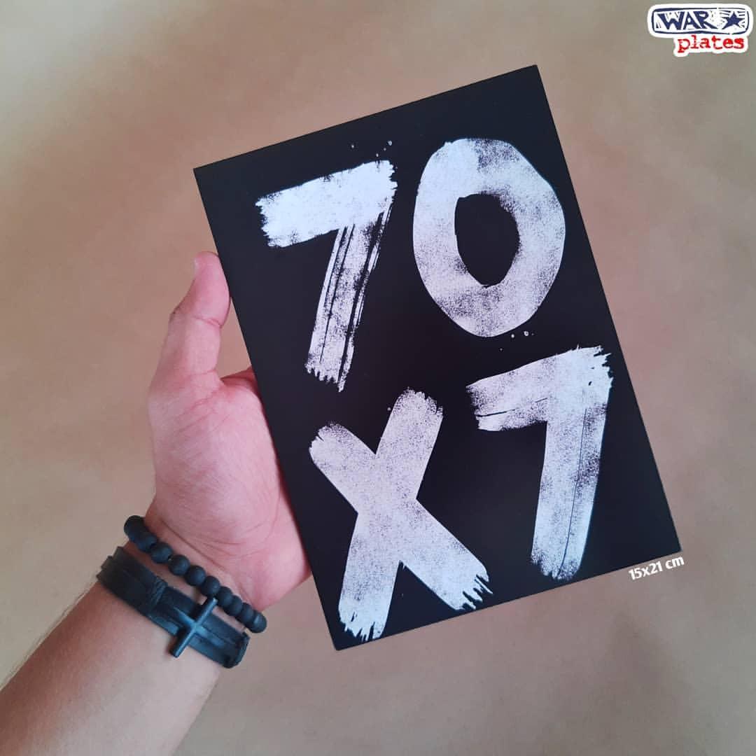 placa escrito setenta vezes sete em número na mão de uma pessoa