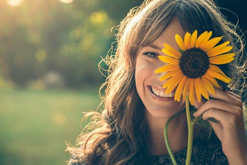 mulher com um girassol na mão sorrindo
