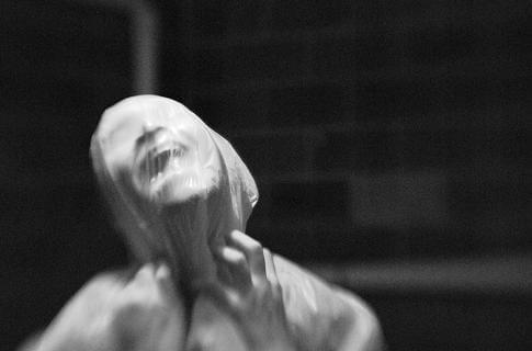 Imagem em preto e branco de uma pessoa com cara de desespero com rosto envolto por um material que a asfixia.