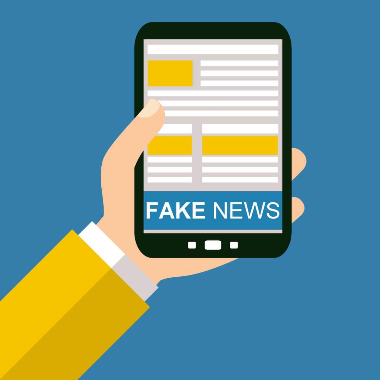 celular na mão de uma pessoas escrito fake news