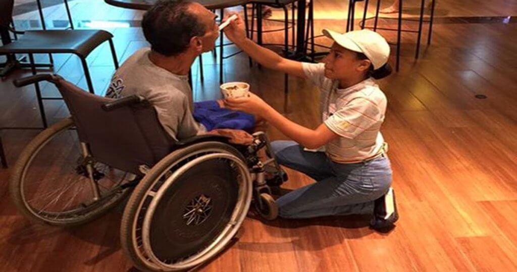 mulher dando sorvete pra um cadeirante sem os braços