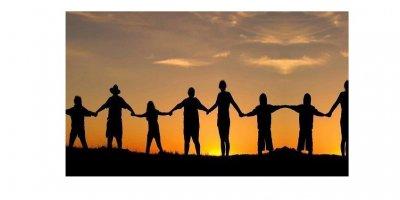 Imagem em silhueta. Grupo de pessoas com maõs dadas em fileira em pôr do Sol.