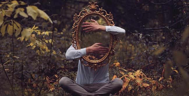 Imagem de uma pessoa, sentada com perna de índio, em uma floresta. Ela abraça um espelho que cobre seu rosto.