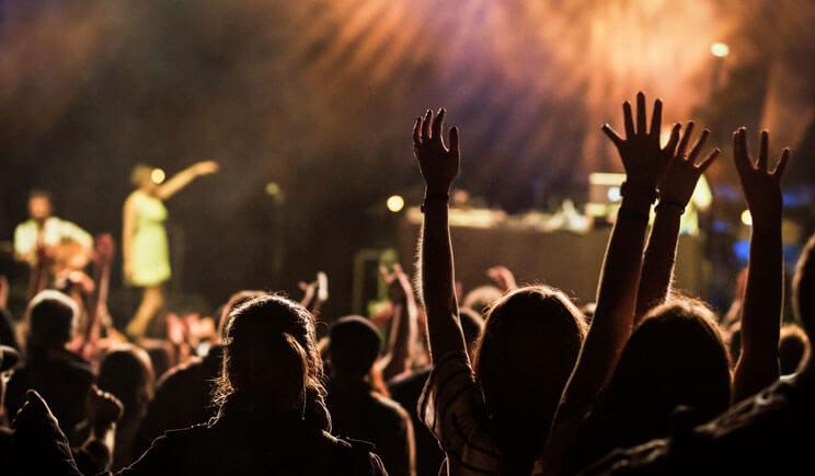 pessoas com as mãos erguidas louvando à Deus