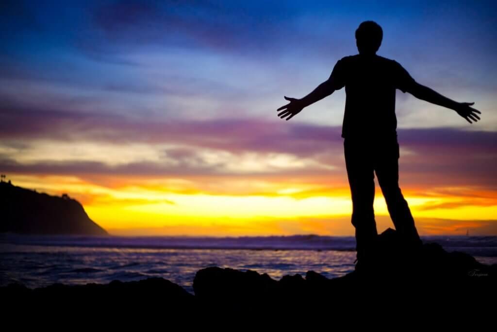 homem de braços abertos em cima de uma pedra em frente ao mar