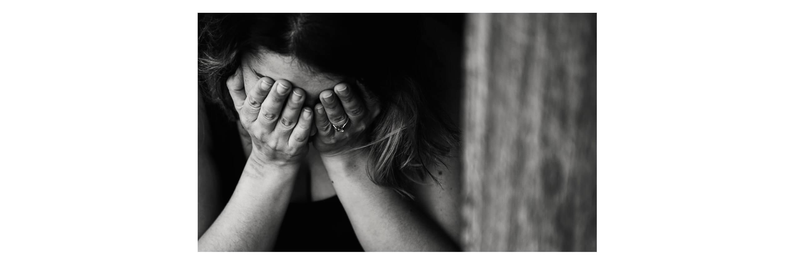 Imagem em preto e branco. Mulher com o rosto abaixado e com as mãos sobre o rosto.