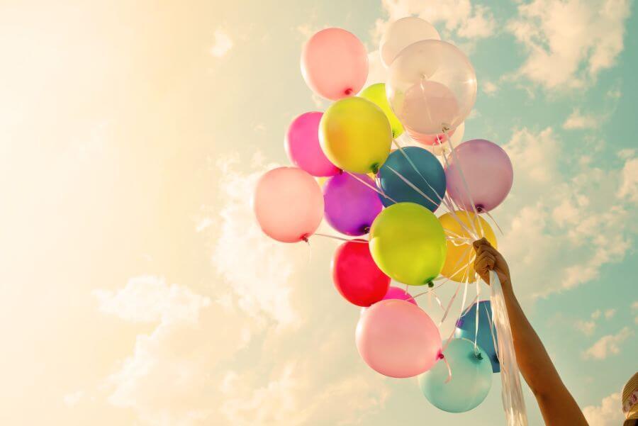 Imagem com céu no fundo. Pessoa segundando balões coloridos com a mão para cima.