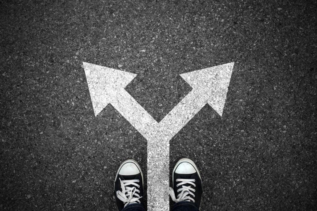Imagem em preto e branco. Dois pés  calçados e à frente deles duas setas indicando caminhos opostos.