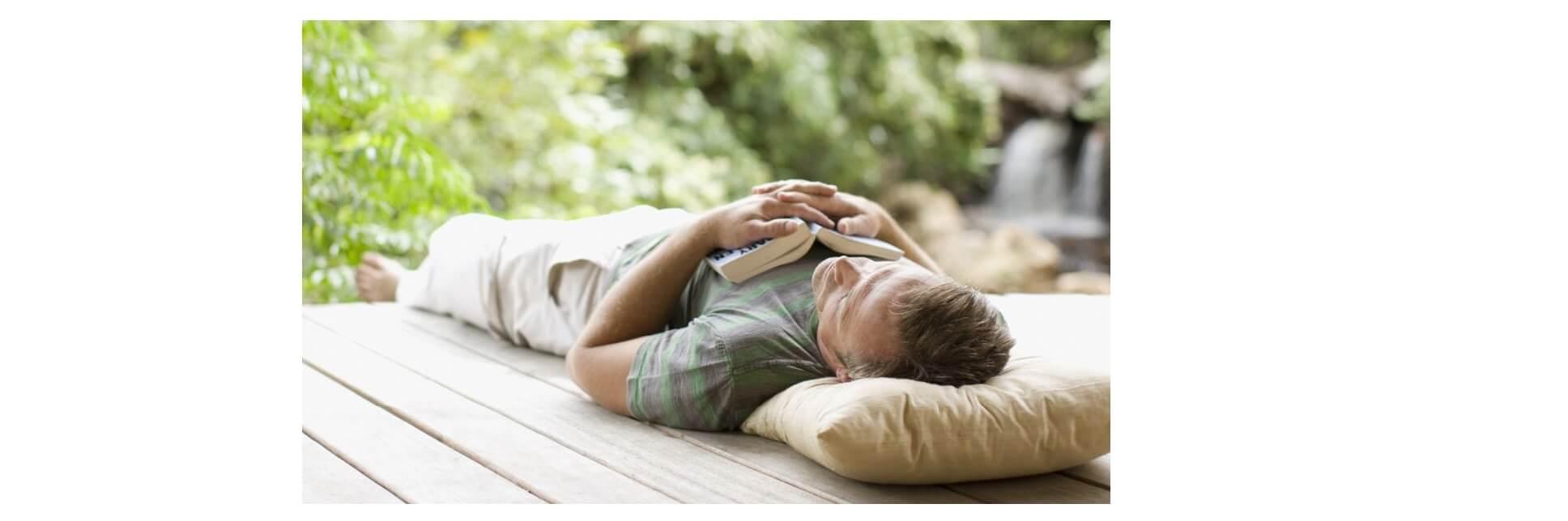 Imagem de um homem deitado com um livro aberto sobre seu peito.