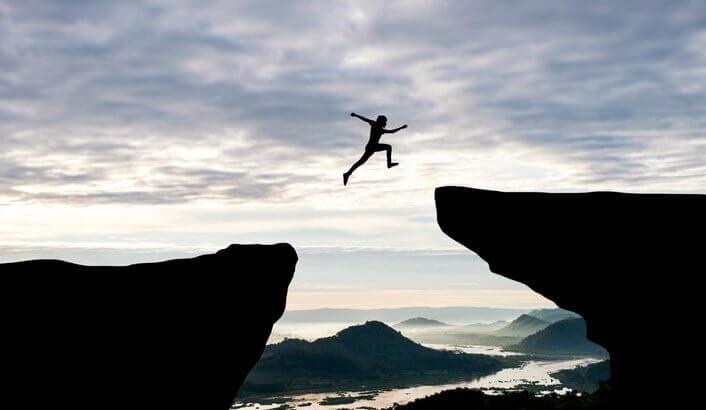 Imagem em silhueta de uma pessoa saltando de uma rocha para outra com um grande vão entre elas.
