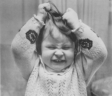Imagem em preto e branco. Criança com expressão de impaciência agarrando seus cabelos com as mão para cima.