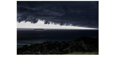 Fotografia de uma tempestade se formando na orla da praia.