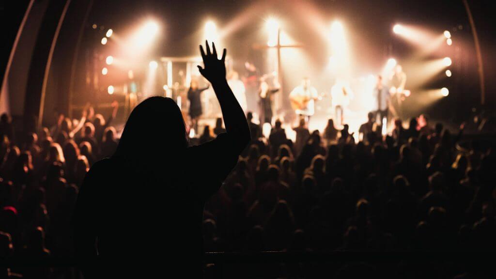 Imagem em silhueta. Pessoa em meio a uma plateia com a mão direita levantada.