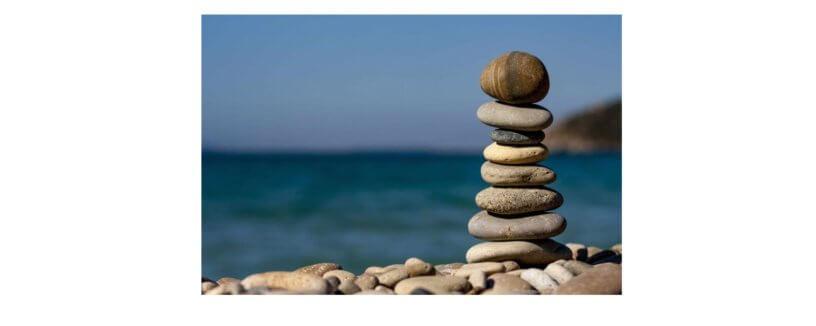 Praia no fundo da imagem. Colunas de pedras sobrepostas em destaque à frente da imagem