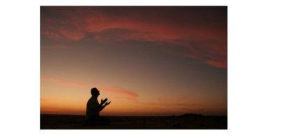 Imagem do pôr do sol com a forma de uma pessoa em silhueta com as mãos estendida para céu.