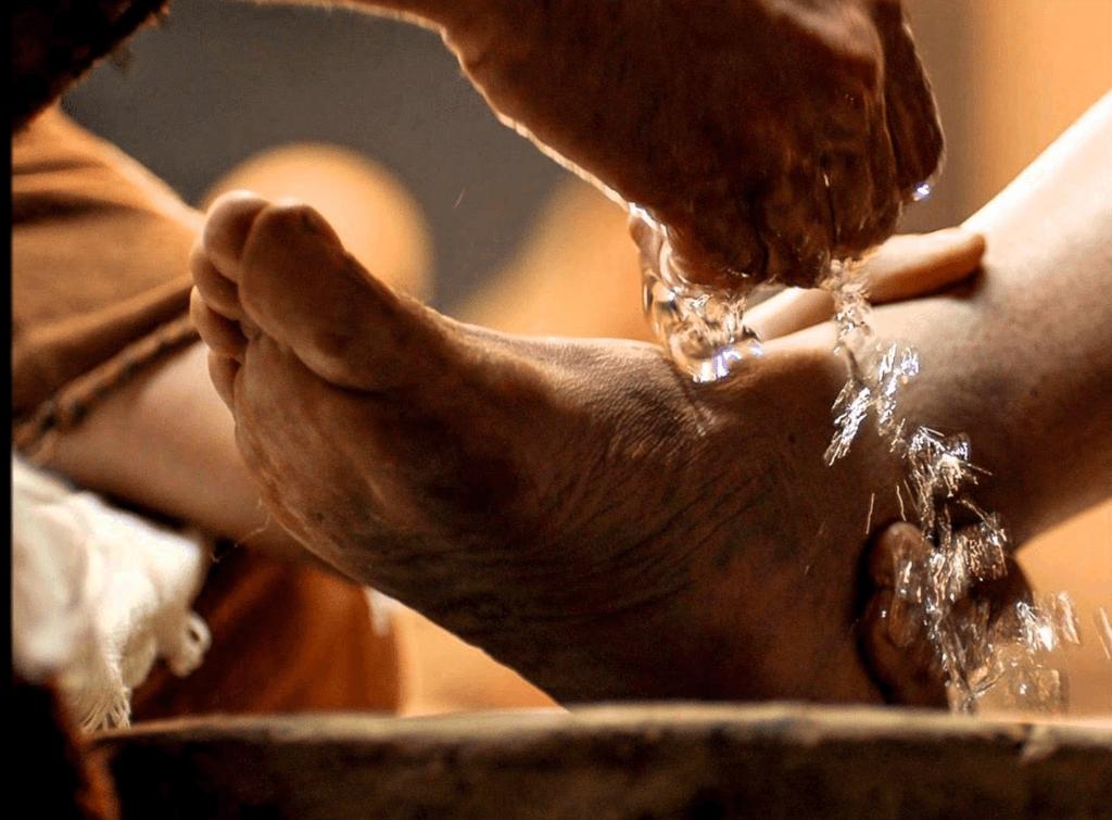 Imagem de um pé estendido sobre uma bacia. O pé é lavado por outra pessoa que o segura pela mão esquerda e joga água sobre o pé com a mão direita.