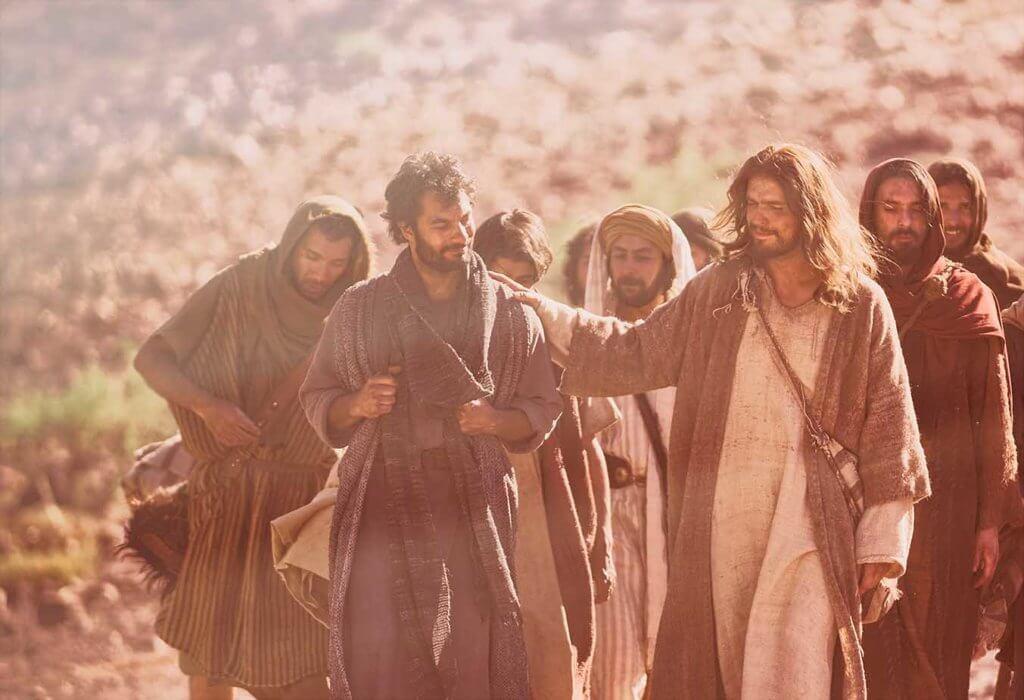 Imagem de Jesus andando com seus discípulos em um local desértico.