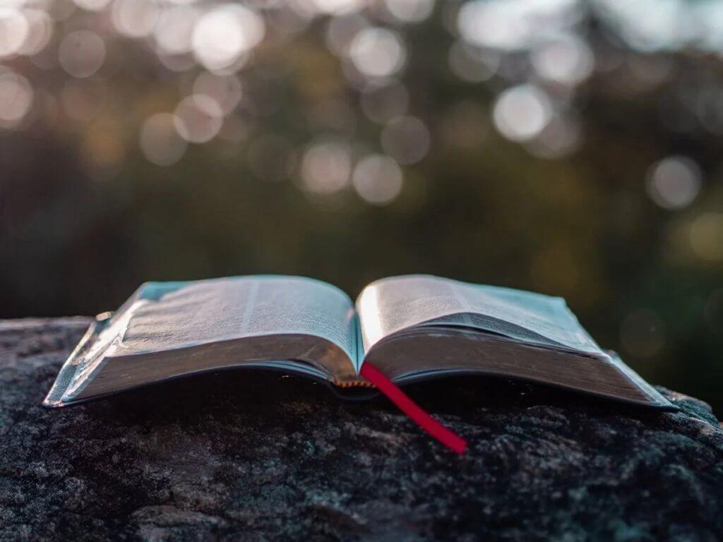 Imagem de uma bíblia aberta sobre uma rocha.