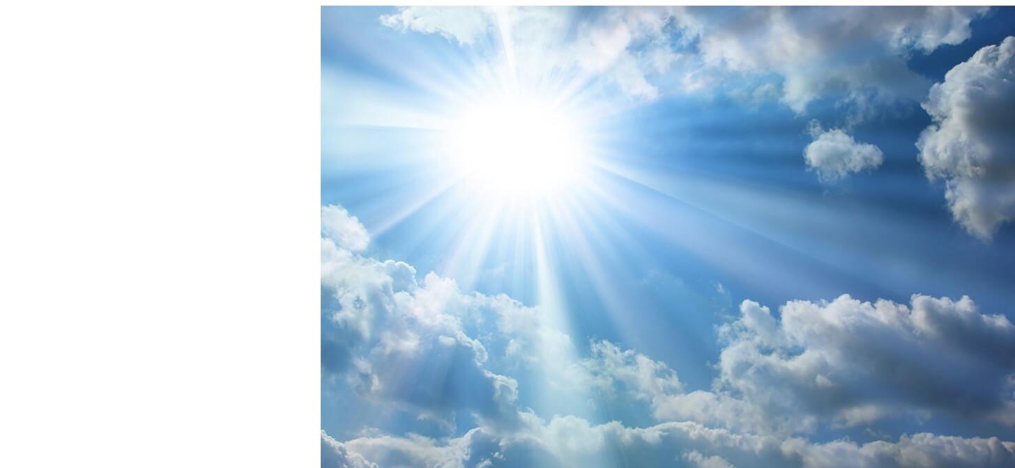 Imagem de um céu azul com nuvens brancas e raios de Sol.